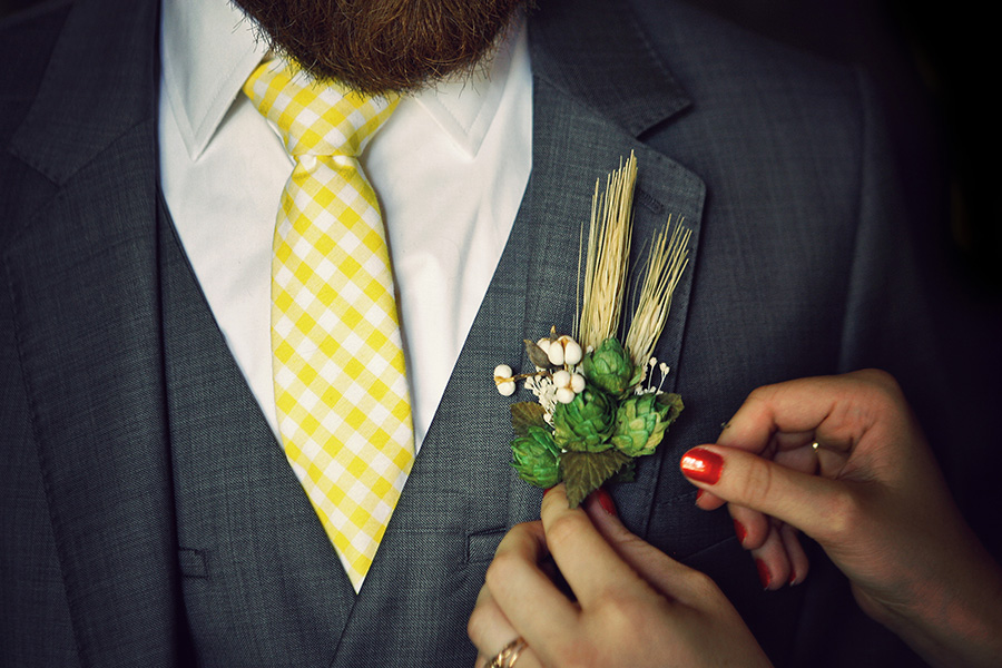 Groom getting a boutonniere pinned on his coat