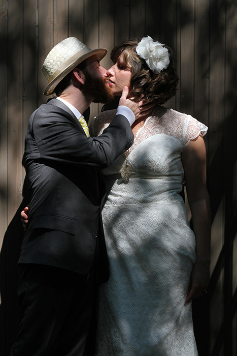 Bride and groom portrait kissing in the shadows