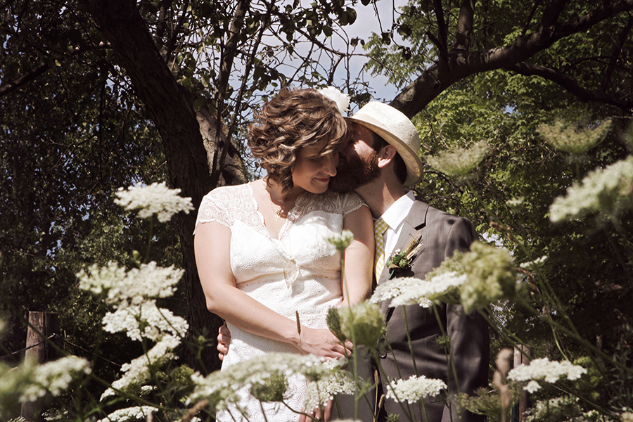 Bride and groom kissing surrounded by flowers
