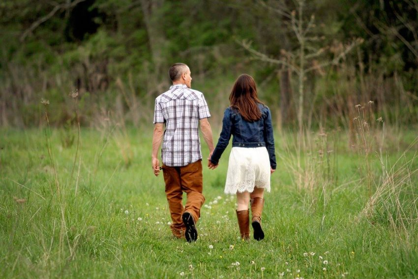 engagement photography couple walking away in a green field holding hands