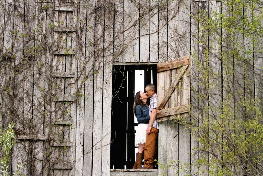 engagement photography couple kissing in a rustic barn doorway