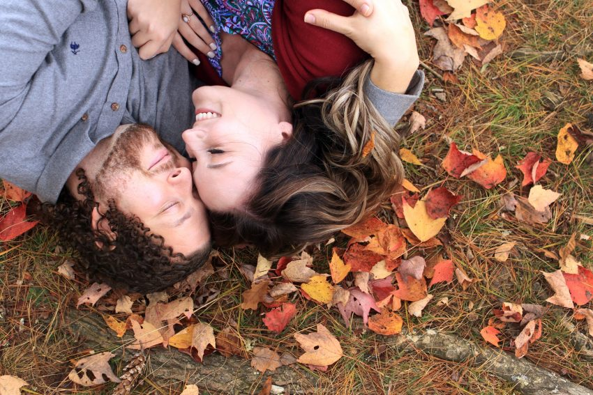 engagement photography couple laying in fall colored leaves smiling