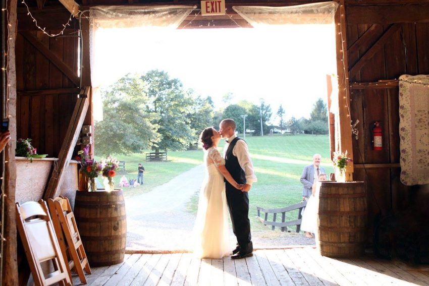 Bride and Groom kiss in the doorway of the barn wedding.