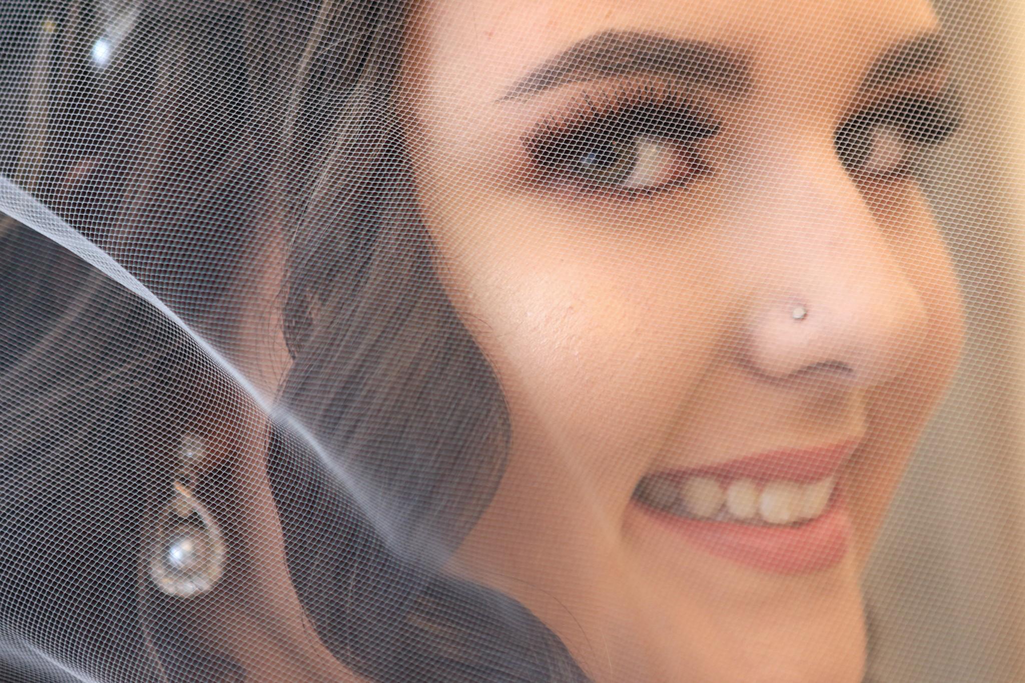 bride under veil smiling