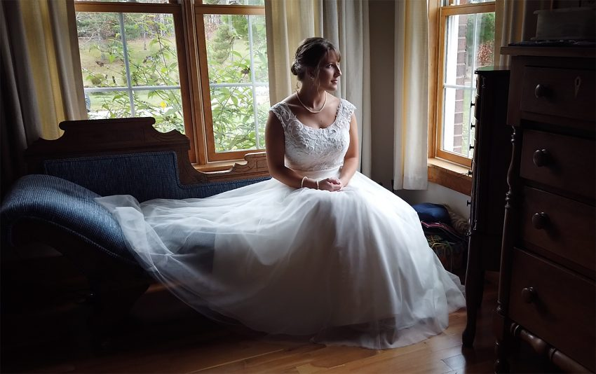 bride in the dress on a sofa looking out the window