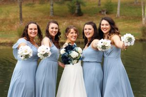 country wedding bride with her bridesmaids holding out thier bouquets