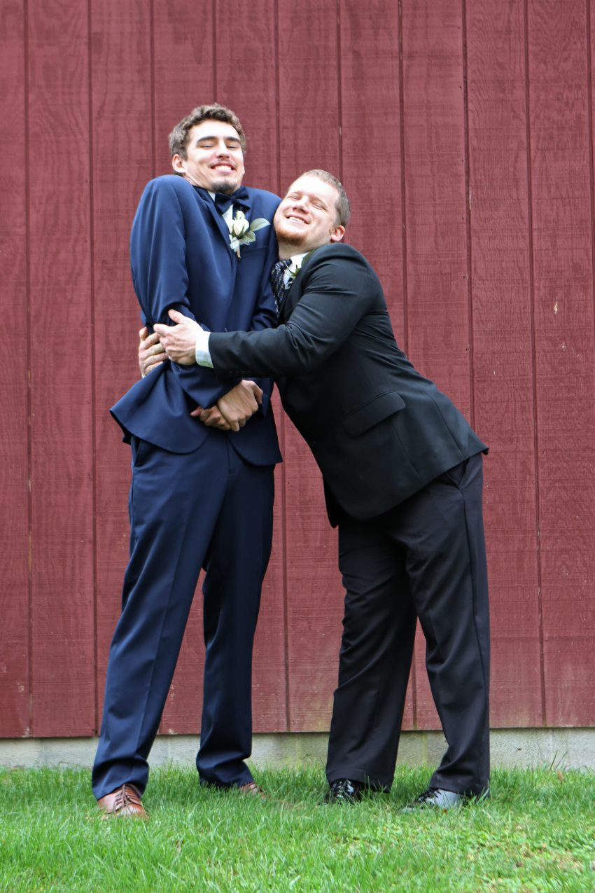 wv country wedding groomsman hugging the groom