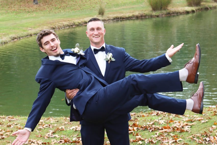 wv country wedding groomsman holding the groom and laughing