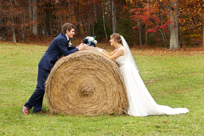 wv country wedding bride and groom pose with a hay bail